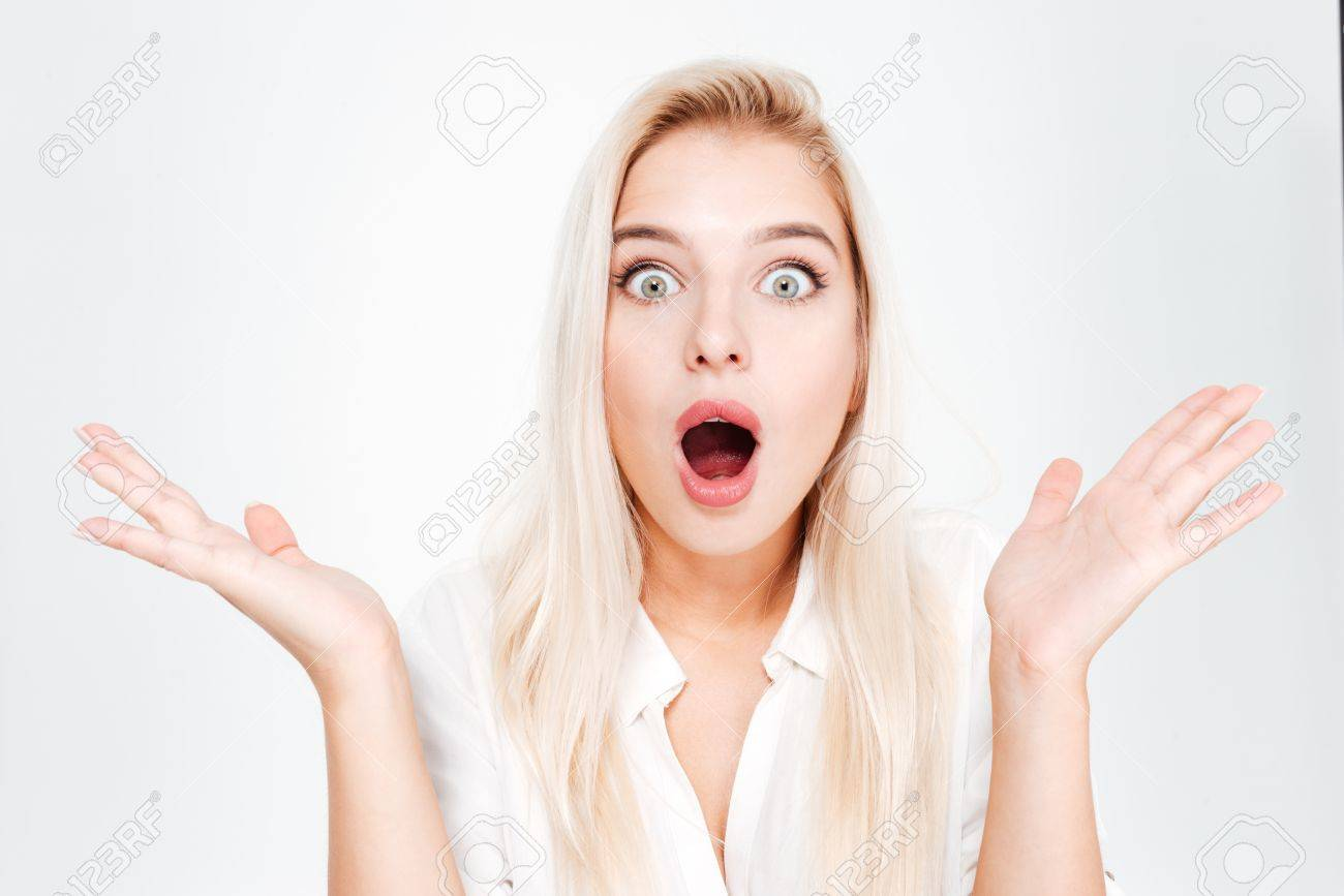 Shocked amazed young woman standing and shouting over white background - 63757523