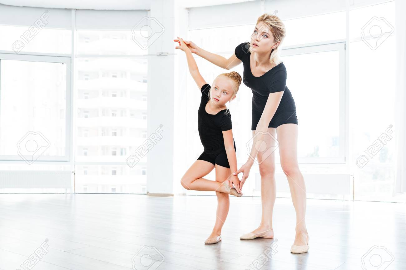 young little girl ballerina learning dance lesson with female