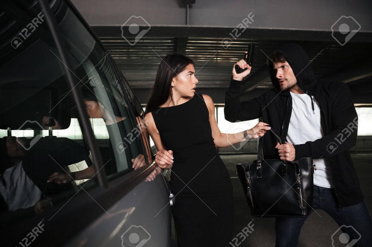 Hombre enojado ladrón en hoodie robar el bolso de la mujer y treatening a ella con el arma en el aparcamiento para coches