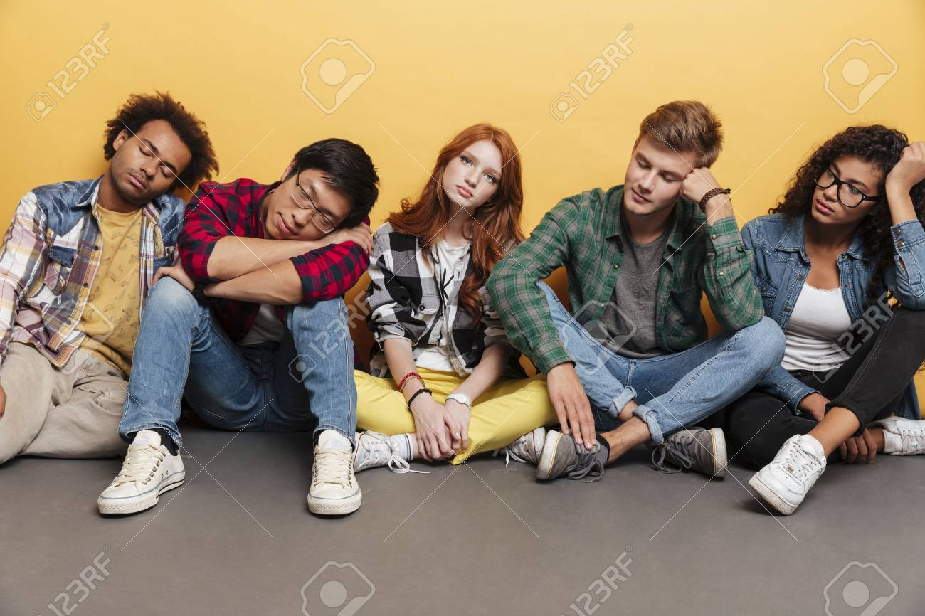 group of tired young people sitting and sleeping over yellow stock
