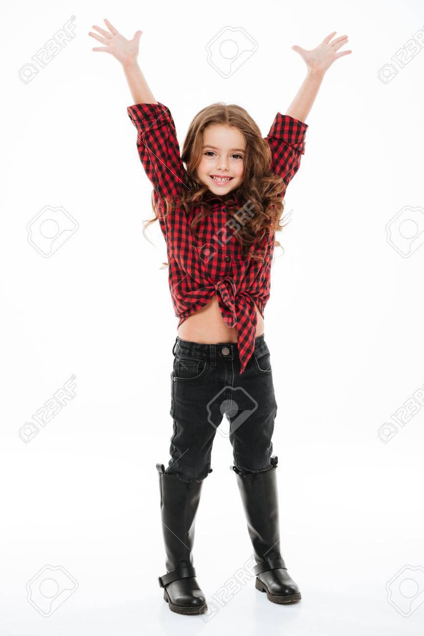 37104452b Foto de archivo - Longitud total de la niña emocionada emocionada en camisa  escocesa de pie con las manos levantadas sobre fondo blanco