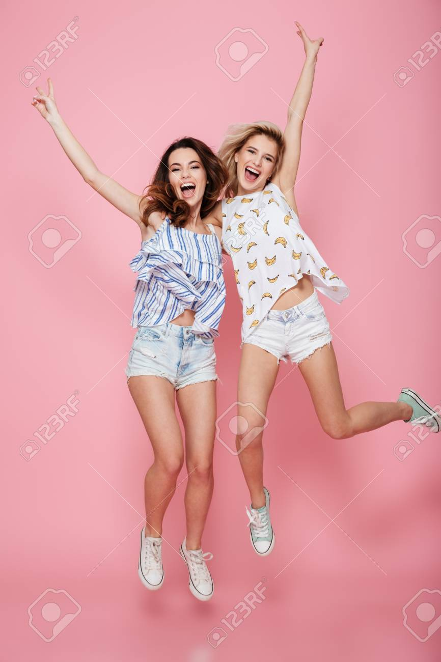 Full length of two cheerful young women showing victory sign and jumping over pink background - 74349513