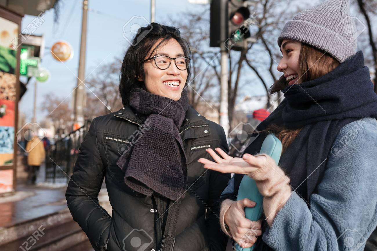 29258fb1102f Photo of happy young asian man wearing glasses and scarf with caucasian  lady talking with each