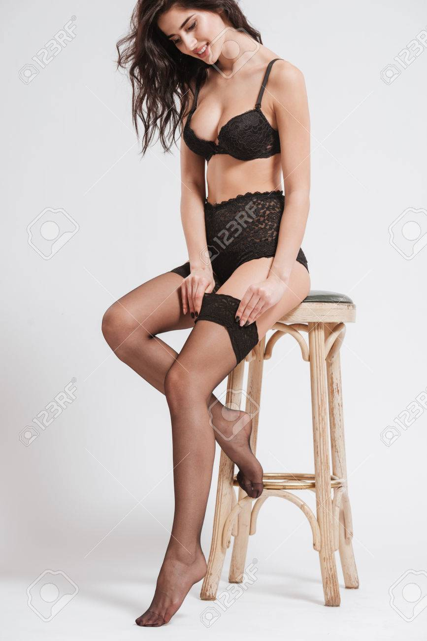 1bcd3c2d3af Full length portrait of a sexy smiling woman wearing lingerie with stockings  and sitting on a
