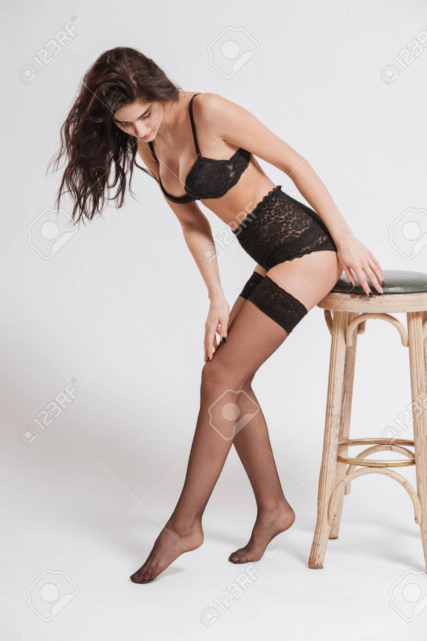 a9ecc1bfdf9 Full length portrait of a young brunette woman wearing lingerie with  stockings and posing on a