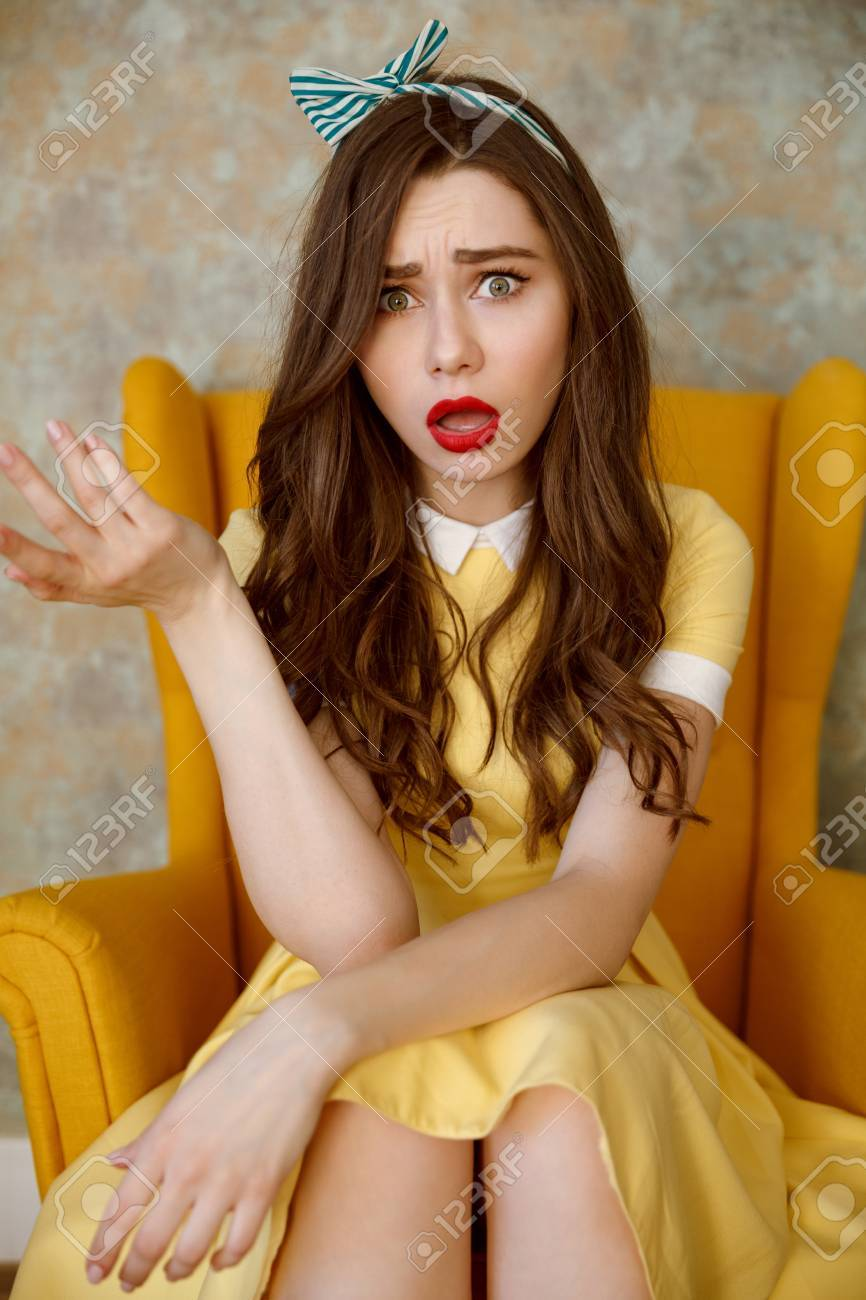 Vertical image of Uncomprehending woman in yellow dress which sitting on armchair and looking at camera Stock Photo - 76326458