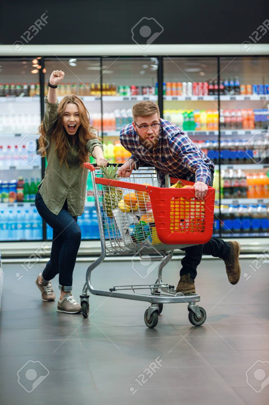 Cheerful Couple Having Fun With The Shopping Cart While Choosing