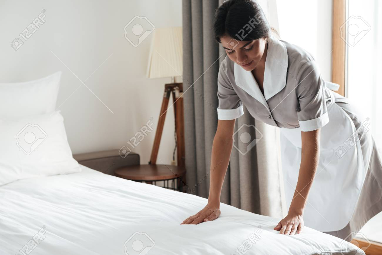 Young hotel maid setting up white bed sheet in hotel room - 80430493
