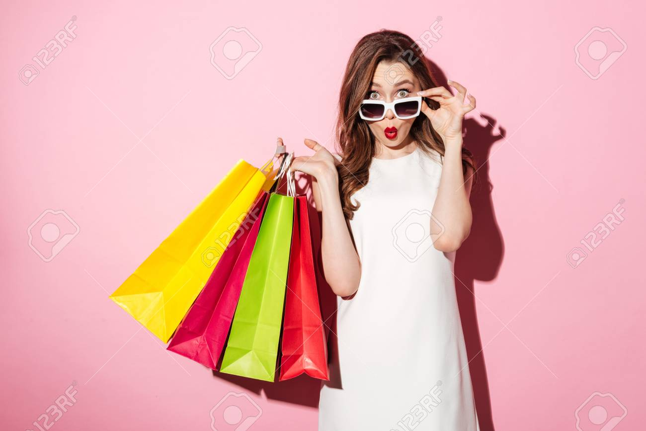 Image of a shocked young brunette lady in white summer dress wearing sunglasses posing with shopping bags and looking at camera over pink background. - 80853874