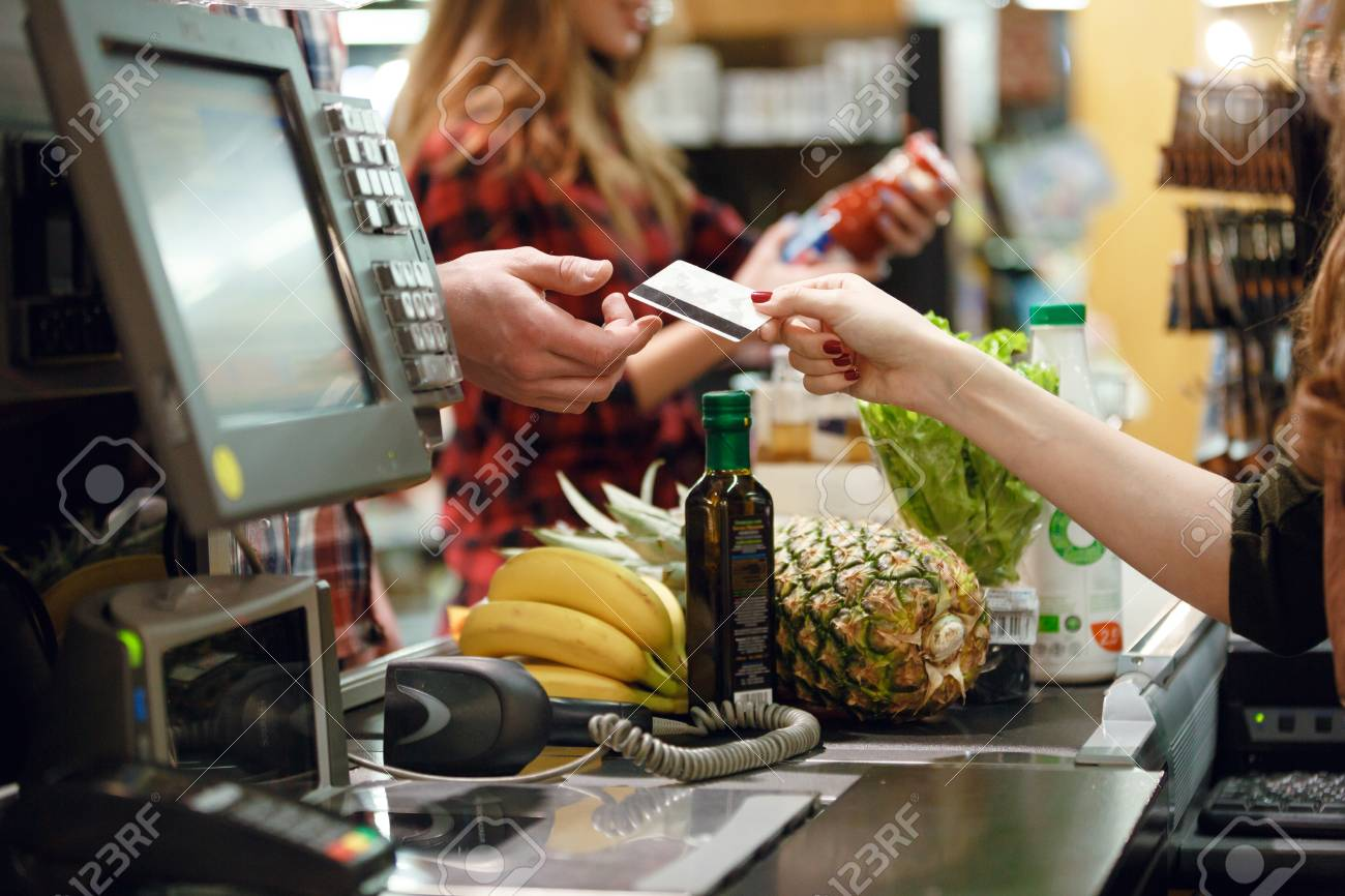 Ananas Credit cropped picture of young man gives credit card to cashier lady
