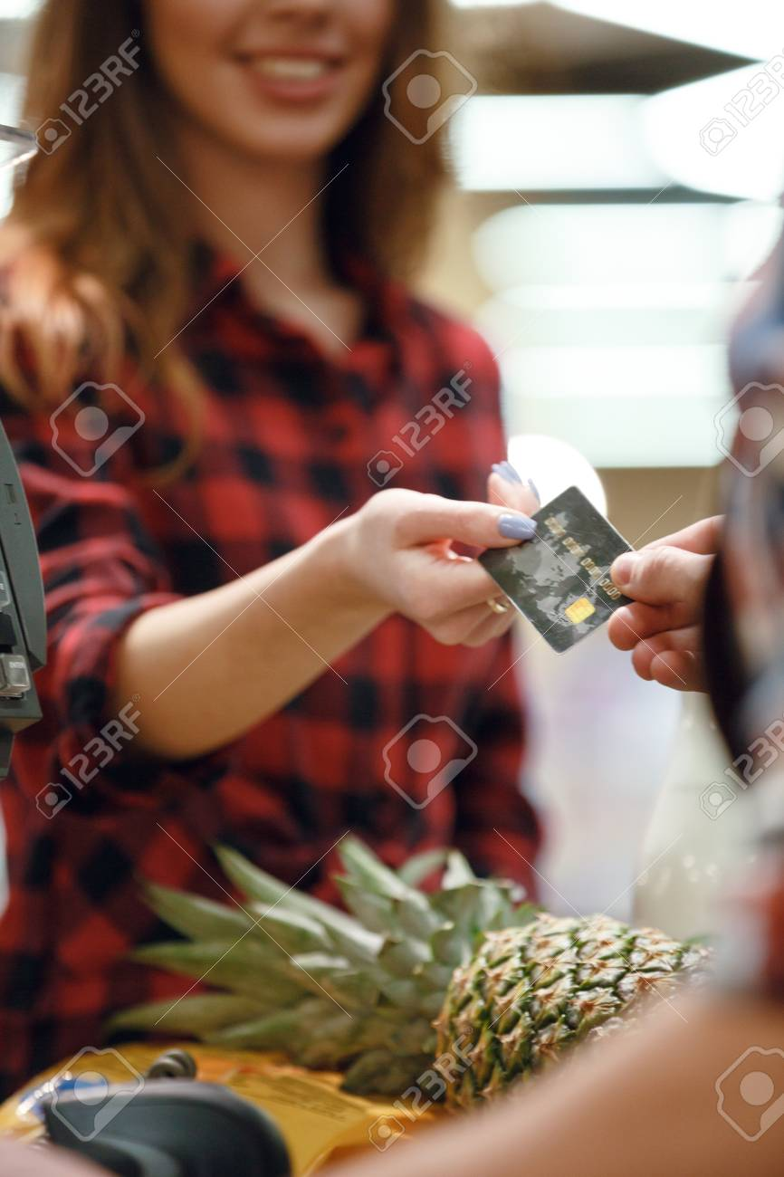 Ananas Credit cropped picture of young woman gives credit card to cashier man