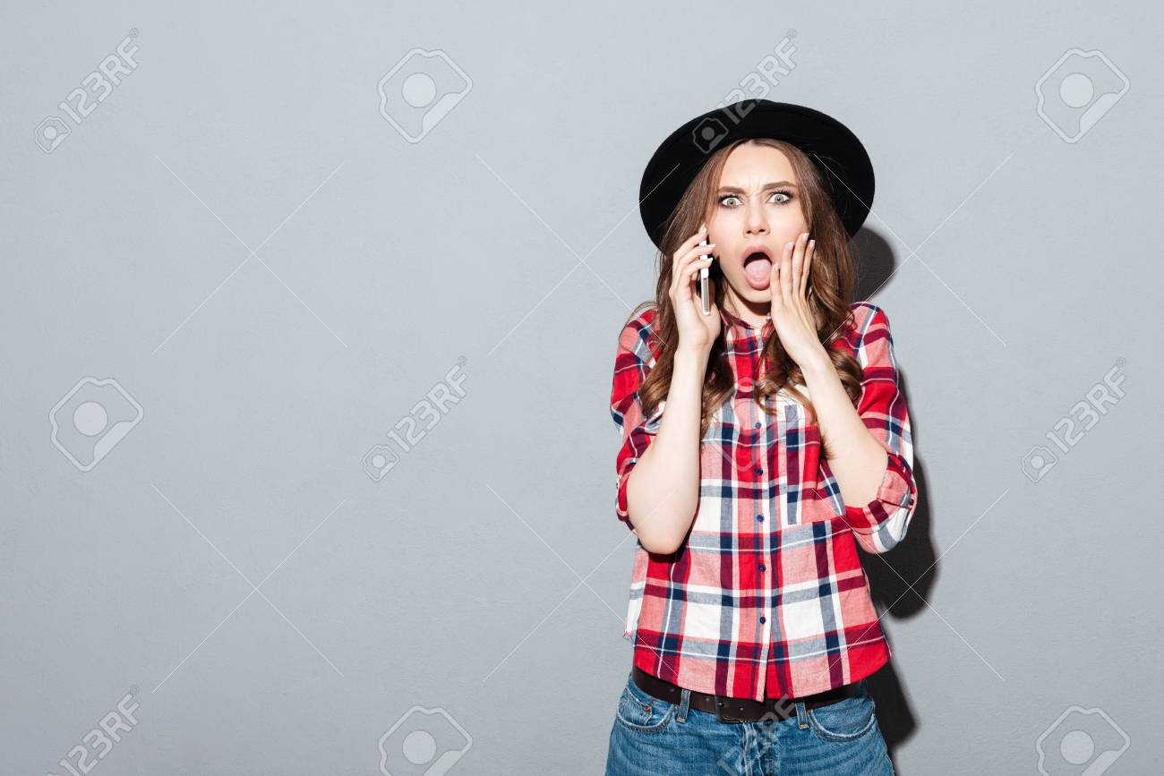 f3238ae6e726f Image of screaming shocked young woman standing over grey wall wearing hat  talking by phone.