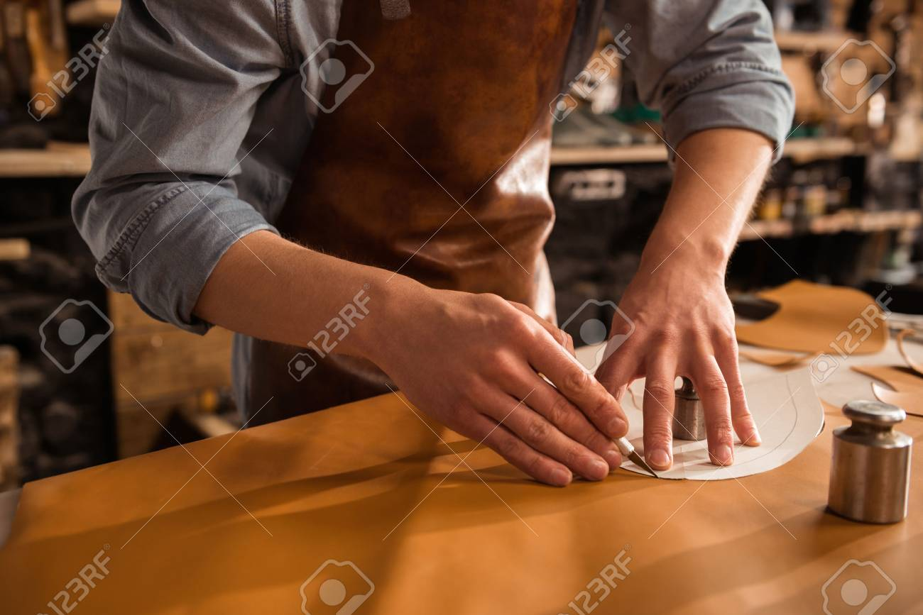 Close up of a shoemaker cutting leather in a workshop - 82350485