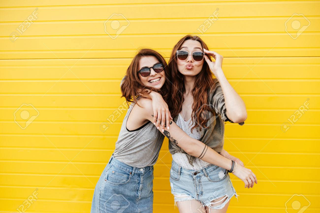 Image of two young happy women friends standing over yellow wall. Looking at camera blowing kisses. - 84291185