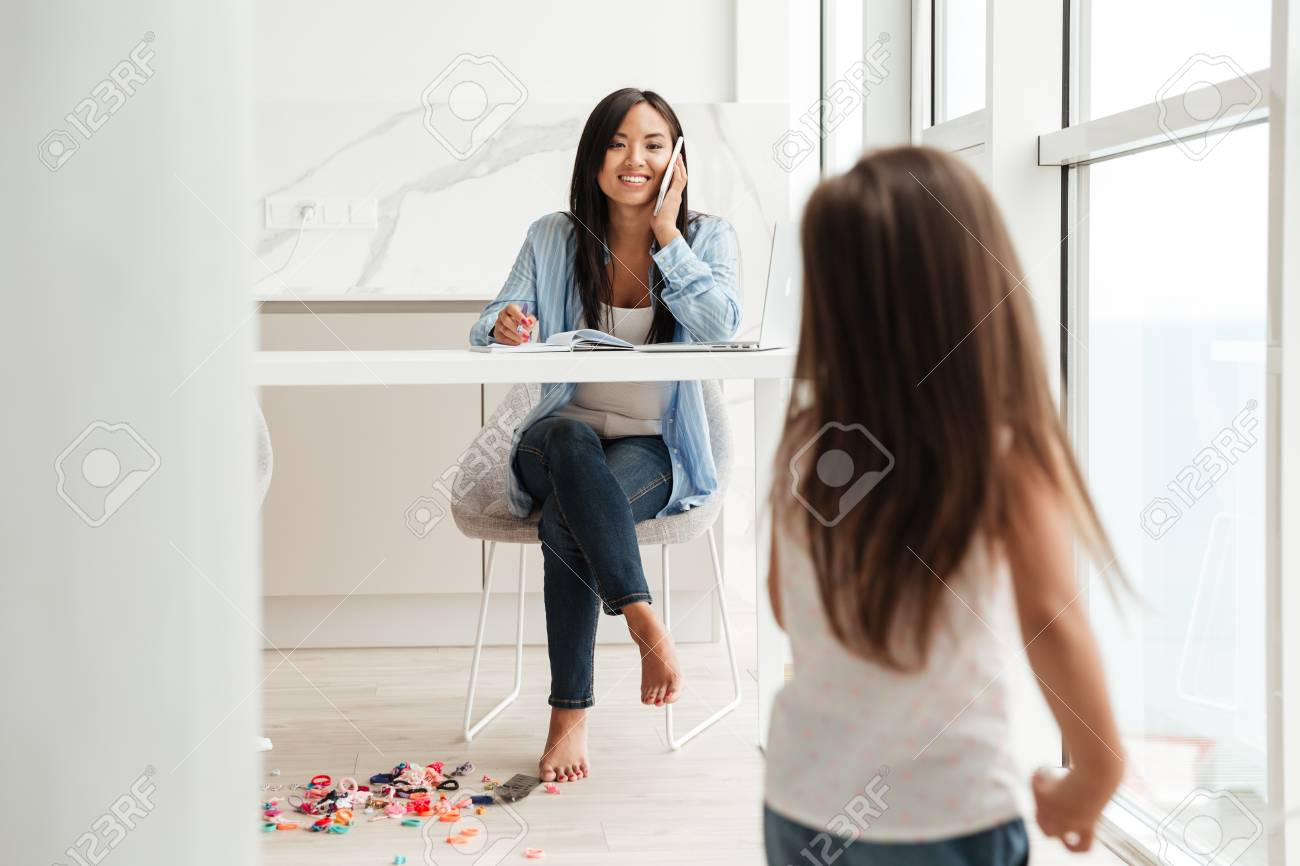Smiling asian woman talking on a mobile phone and working on laptop while her little daughter playing at home - 84527649