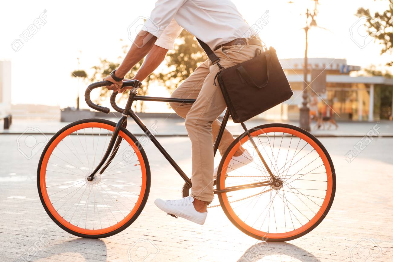 Cropped picture of handsome young african man early morning with bicycle walking outdoors. - 85242832