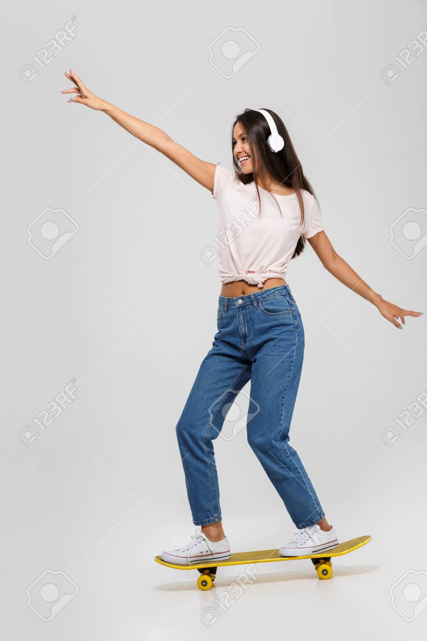 Full length portrait of a happy funny asian woman in headphones listening to music while riding on a skateboard isolated over white background - 88256542