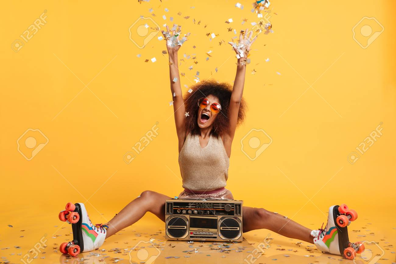 Emotional african disko woman in retro wear and roller scates throwing confetti while sitting with boombox, isolated on yellow background - 89363513