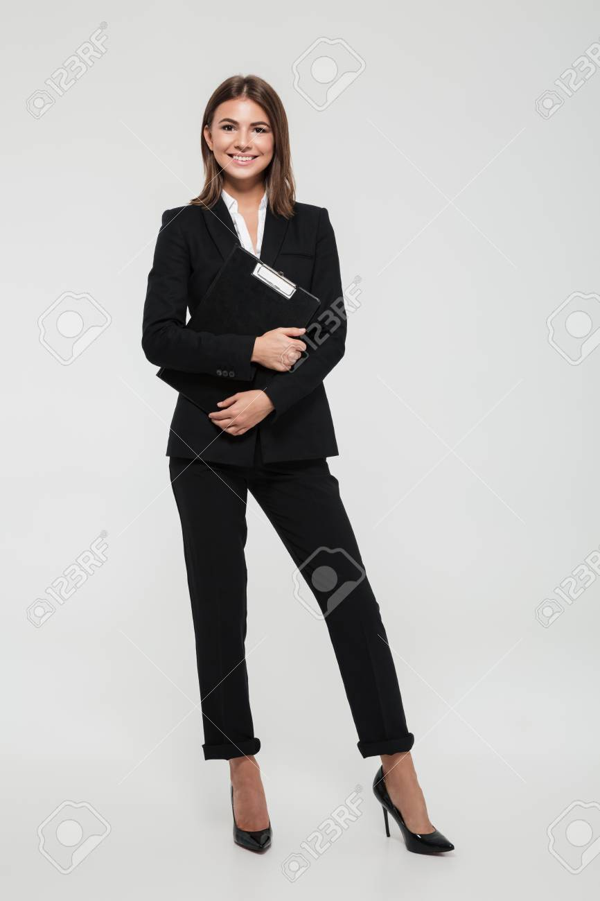 Full length portrait of a happy smiling businesswoman in suit holding clipboard and looking at camera isolated over white background - 89362206