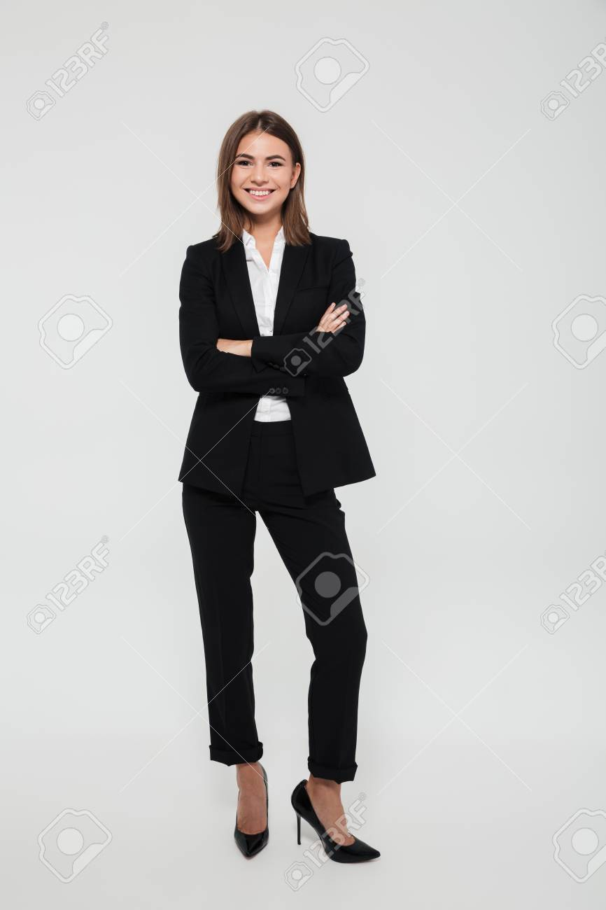 Full length portrait of happy cheerful businesswoman in suit standing with arms folded and looking at camera isolated over white background - 89362852