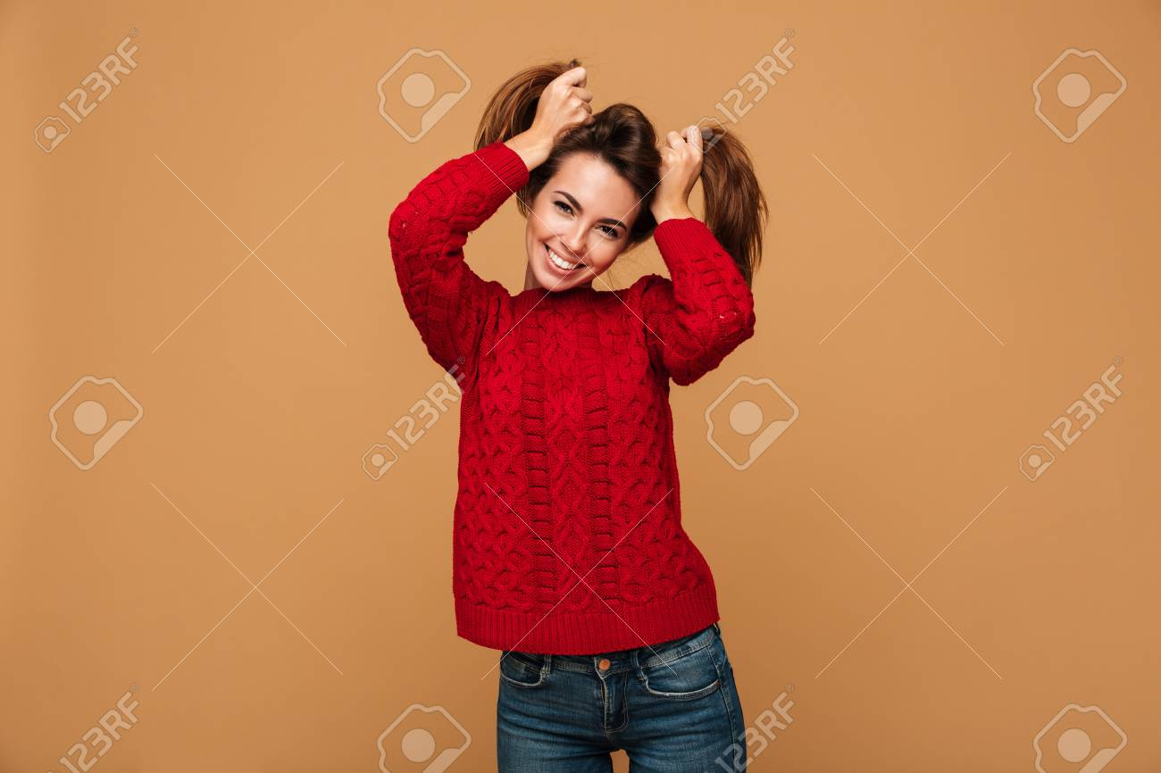 dc9c878a76 Picture of funny caucasian woman dressed in sweater standing isolated.  Looking camera. Stock Photo