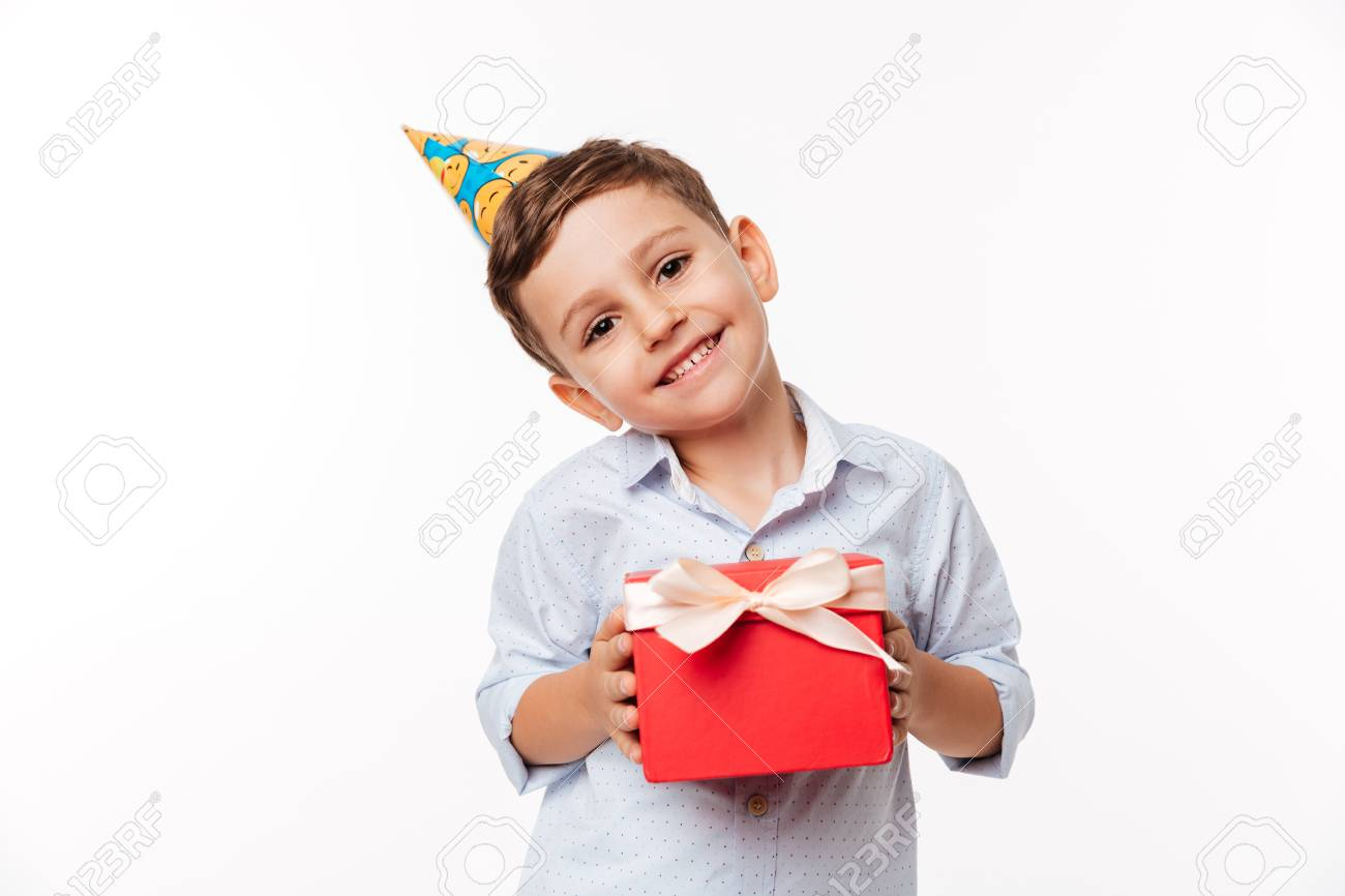 Portrait Of A Lovely Cute Little Kid In Birthday Hat Holding Present Box And Looking