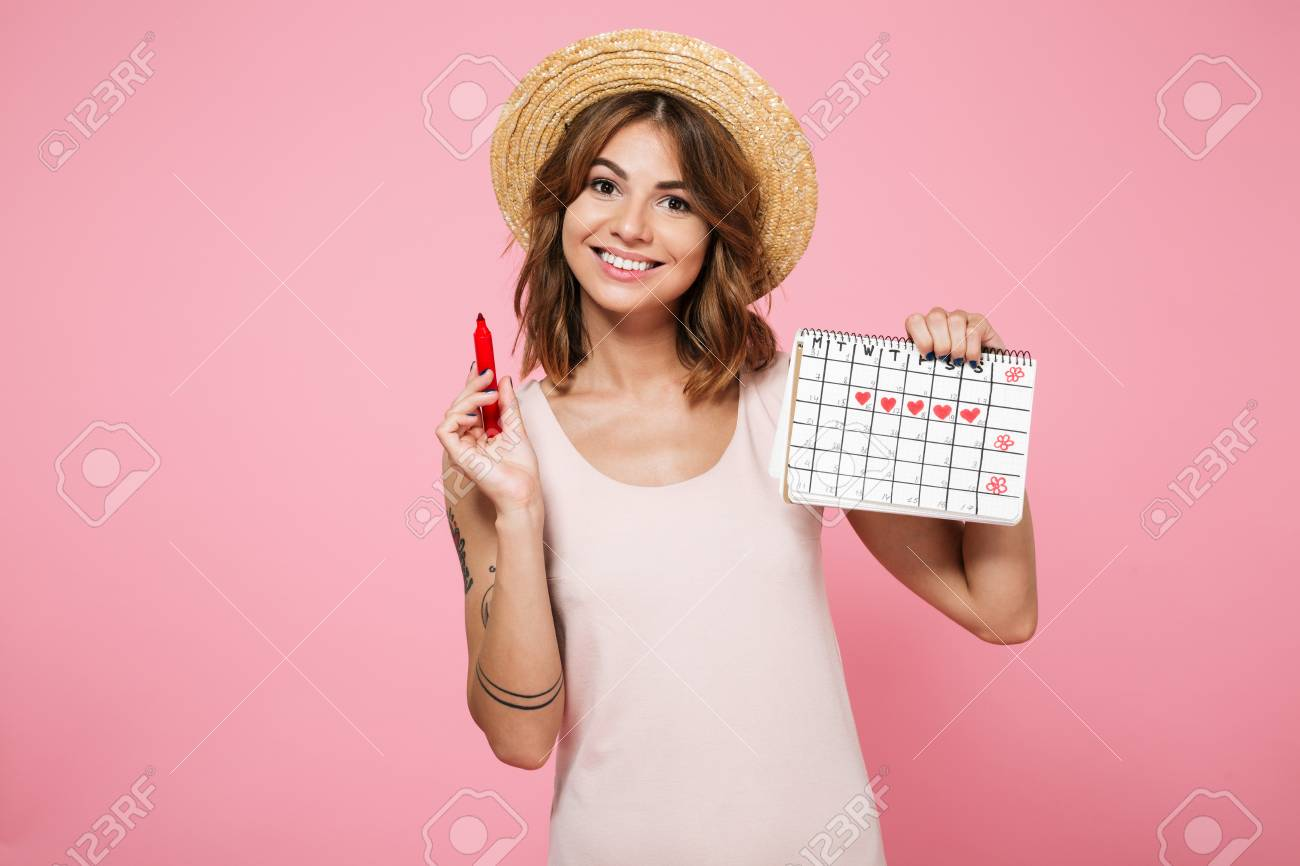 Portrait of a young smiling girl in summer hat checking her periods with a calendar and a felt-tip pen isolated over pink background - 90184107
