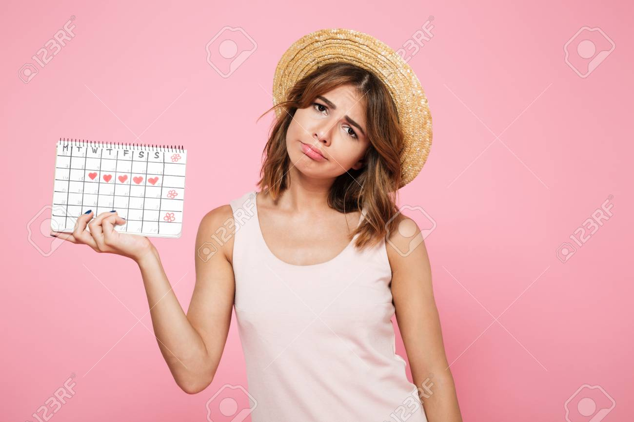 Portrait of a sad unhappy girl in summer hat holding her periods calendar and looking at camera isolated over pink background - 90184134