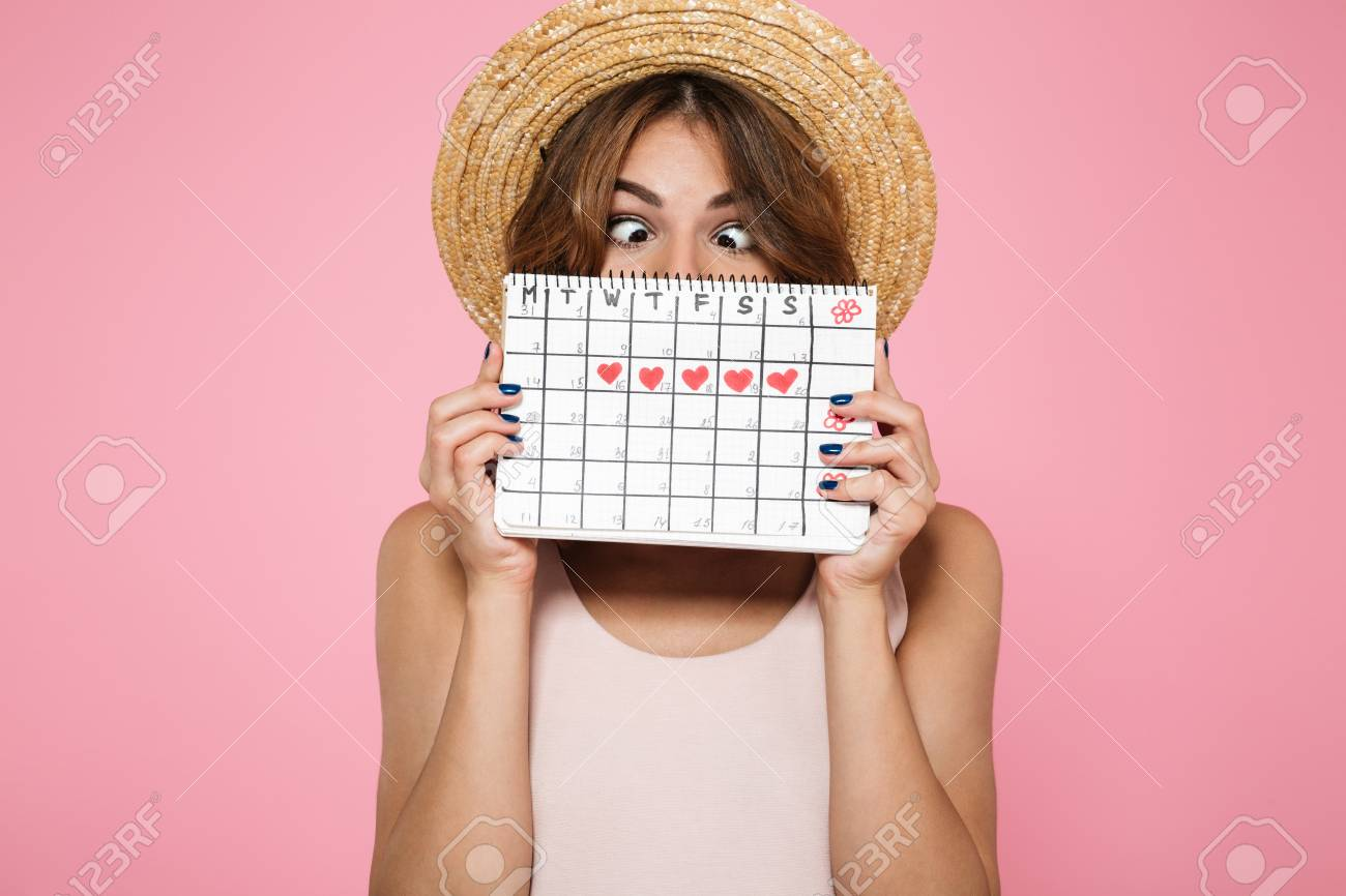 Portrait of a crazy funny girl in summer hat holding and hiding behind a periods calendar isolated over pink background - 90183403