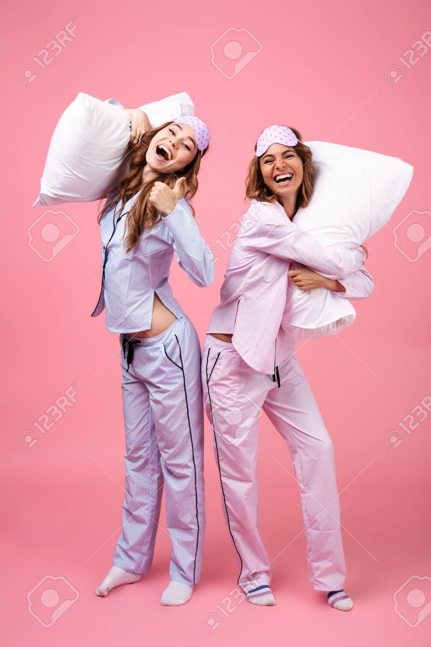 7384327fee Foto de archivo - Retrato de cuerpo entero de dos niñas felices emocionadas  vestidas con pijamas de pie y sosteniendo almohadas aisladas sobre fondo  rosa