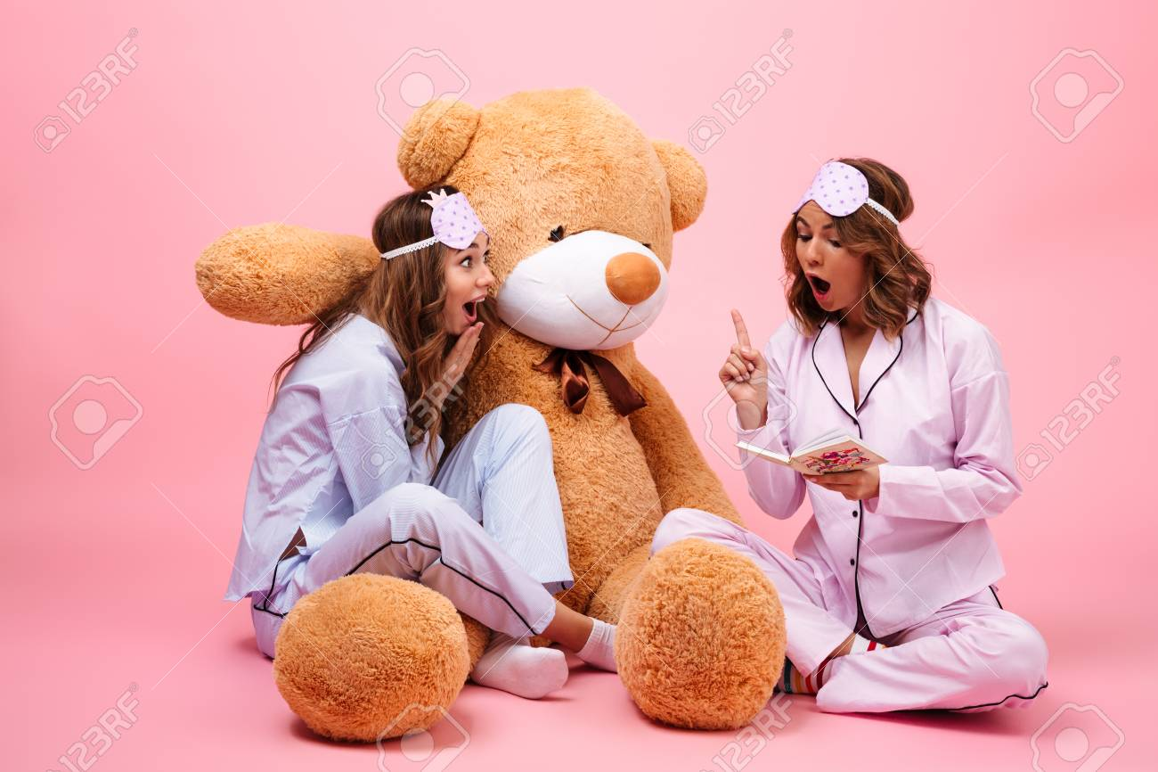 Stock Photo - Two smiling young girls dressed in pajamas sitting with a big  teddy bear and reading a book isolated over pink 17b83a63f
