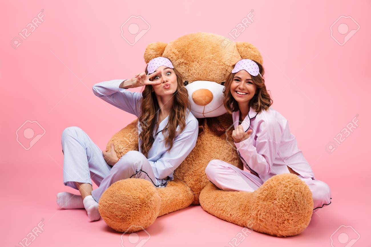 Stock Photo - Two smiling young girls dressed in pajamas sitting with a big  teddy bear and having fun isolated over pink 1a85eb442