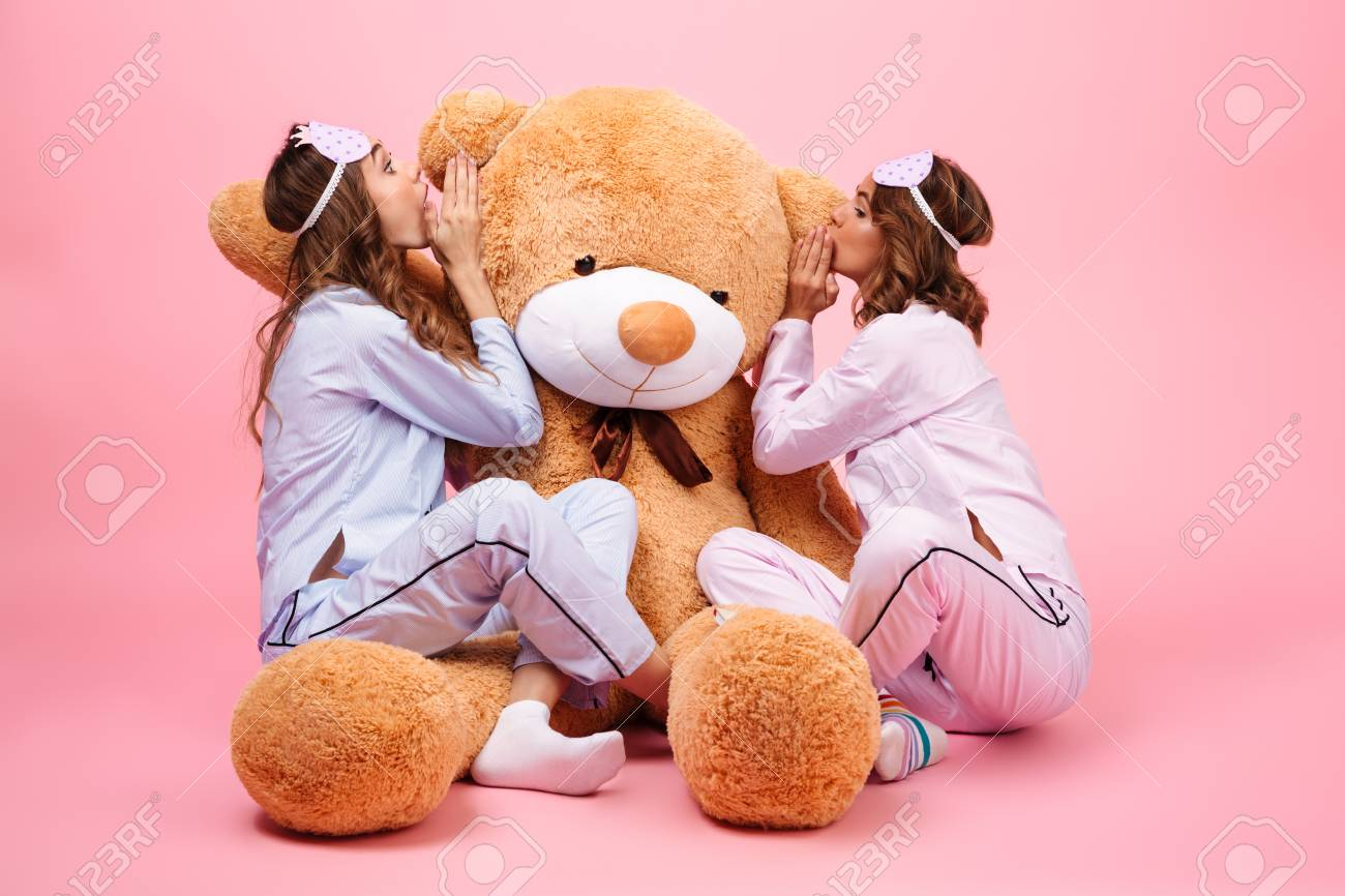Stock Photo - Two girls dressed in pajamas sitting with a big teddy bear  and whispering a secret isolated over pink e6c2e4d23