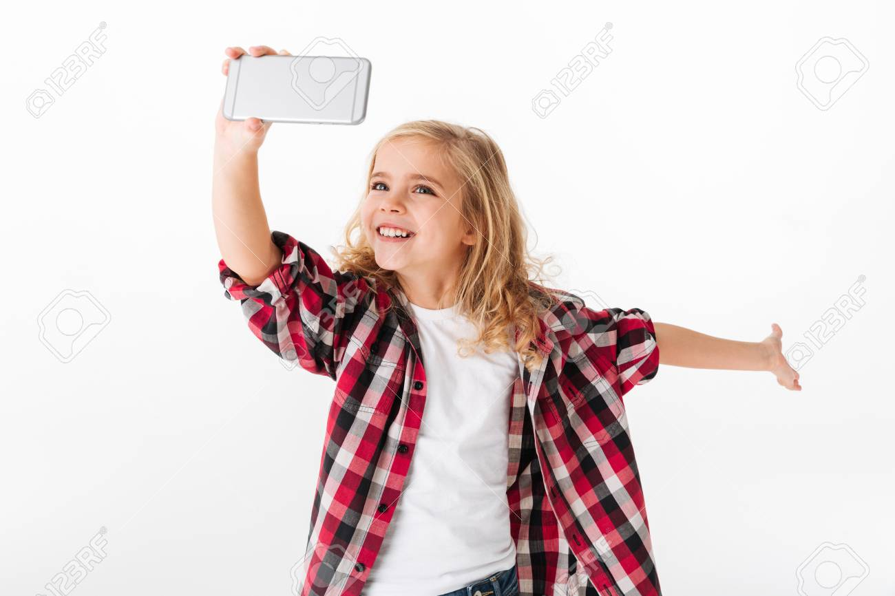Portrait of an excited little girl taking a selfie isolated over white background - 93700231