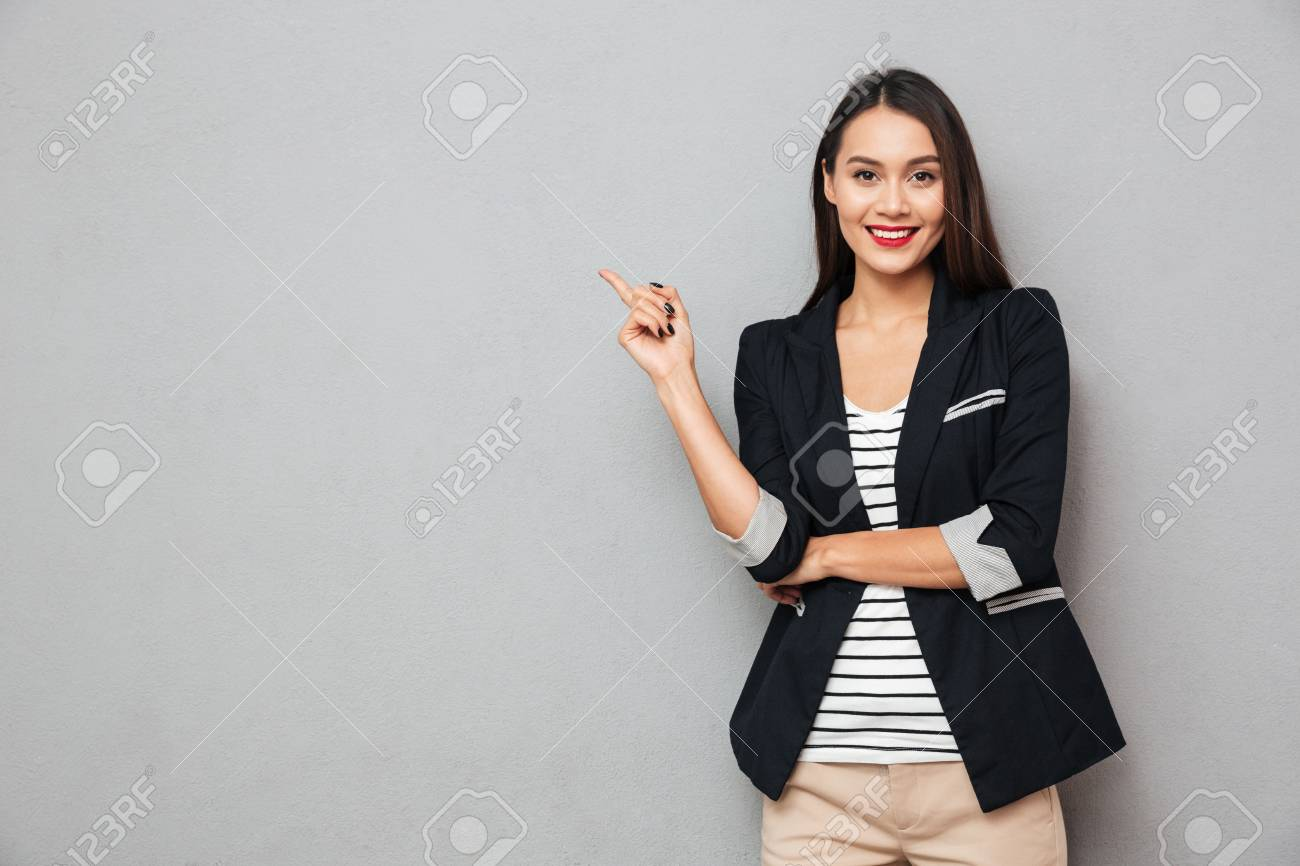 Smiling asian business woman pointing up and looking at the camera over gray background - 94123301