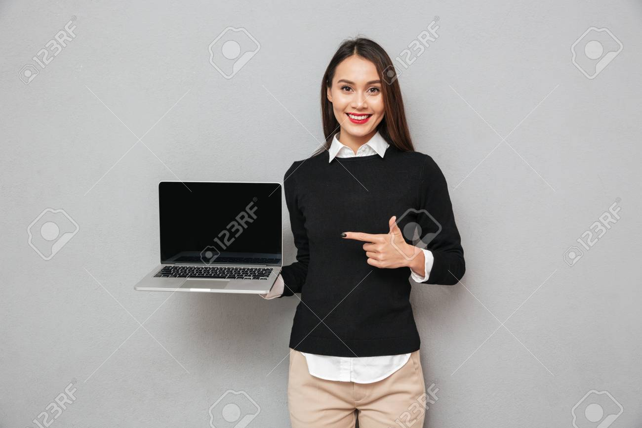 Pleased asian woman in business clothes showing blank laptop computer screen and pointing on it while looking at the camera over gray background - 94076153