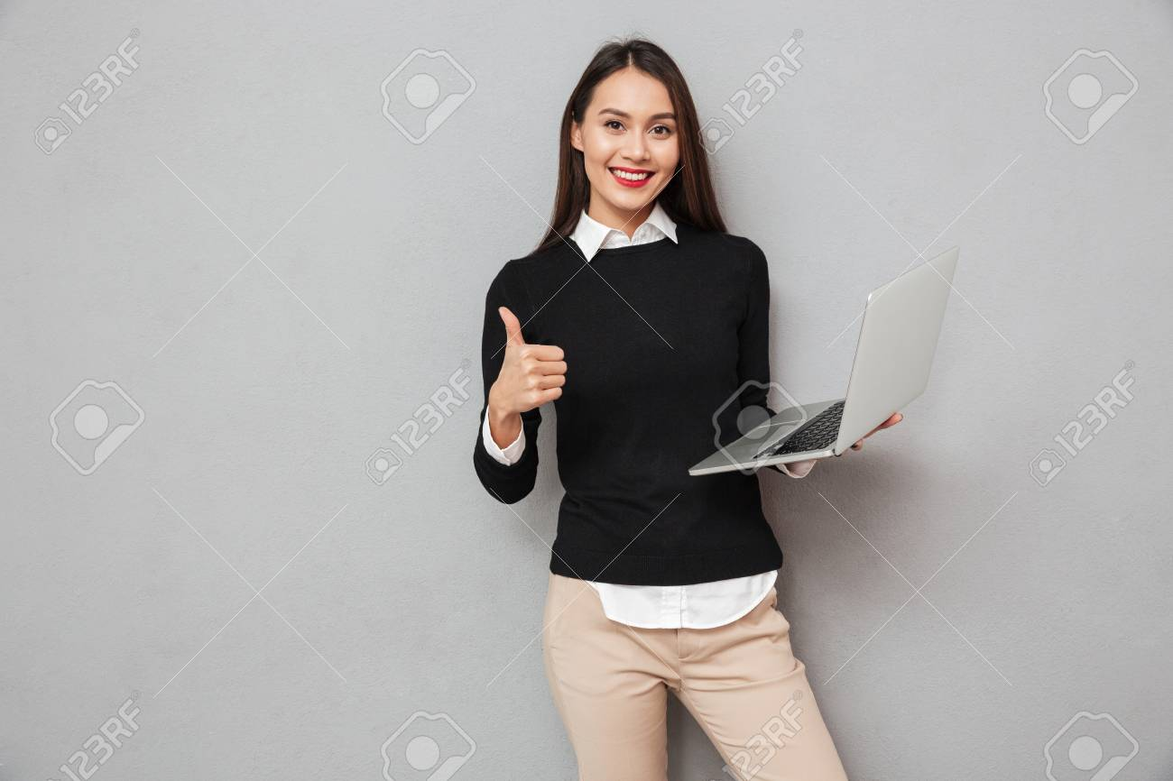 Pleased asian woman in business clothes holding laptop computer and showing thumb up while looking at the camera over gray background - 93811354