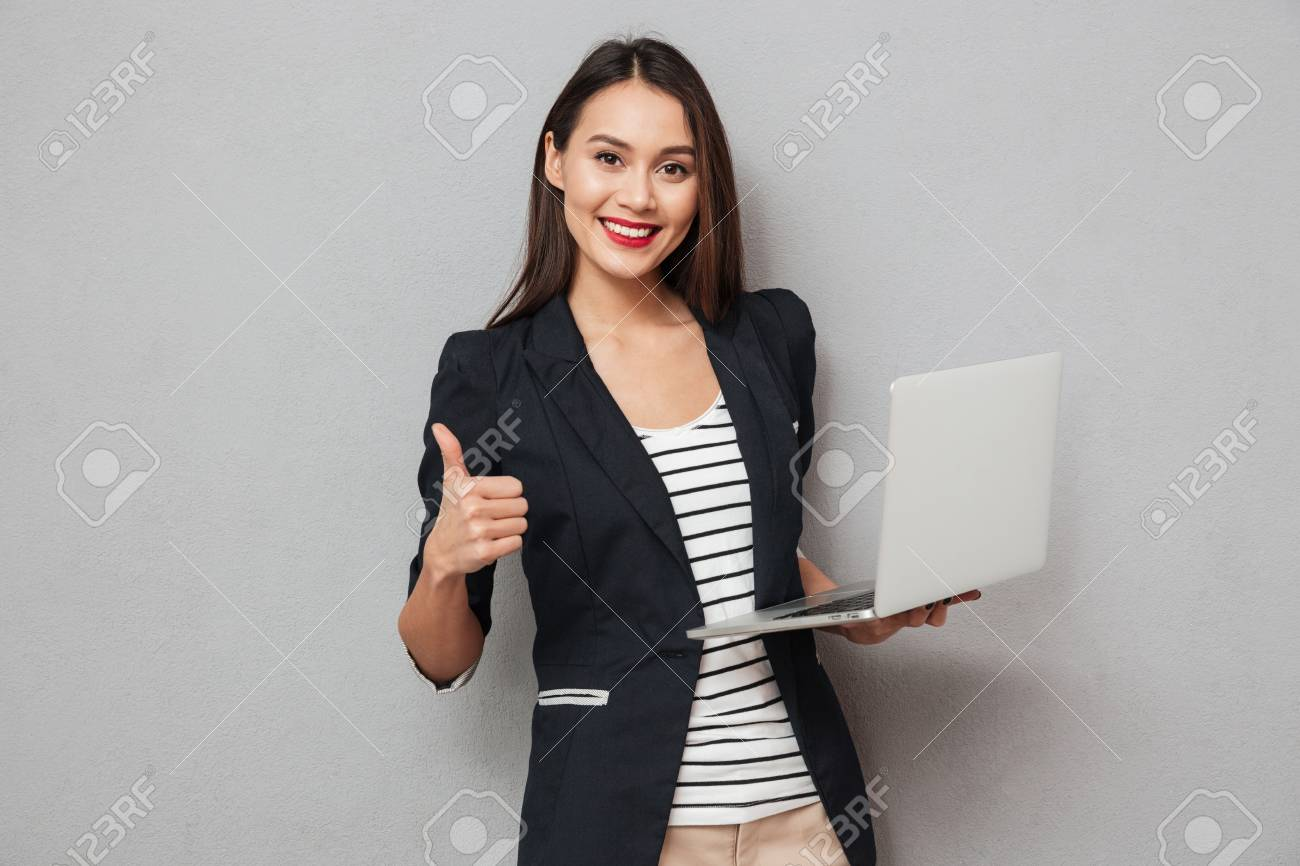 Holding asian business woman holding laptop computer and showing thumb up while looking at the camera over gray background - 93807278