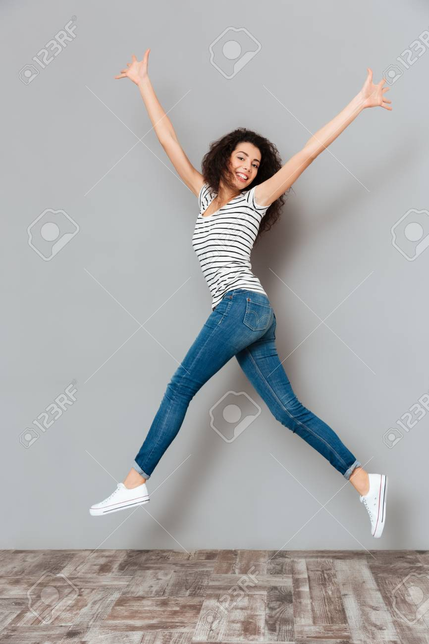 Energetic woman 20s in striped t-shirt and jeans, jumping with hands throwing up in air over grey background - 93811934