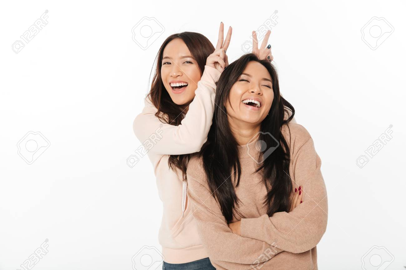Picture of two asian cute ladies sisters standing isolated over white background looking camera have fun. - 93835269