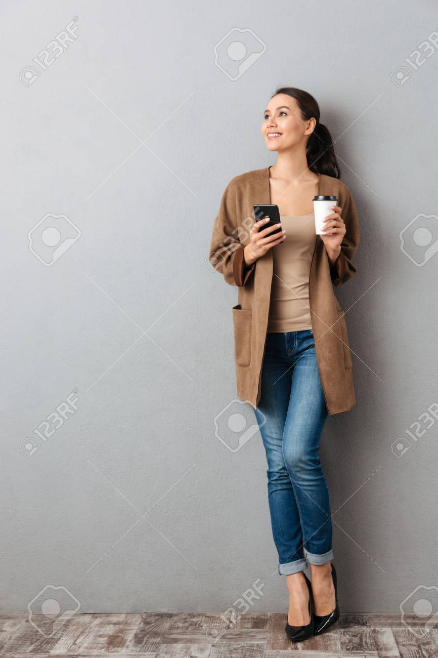 Full length of a beautiful young asian woman holding mobile phone while standing and holding cup of coffee over gray background - 95029486