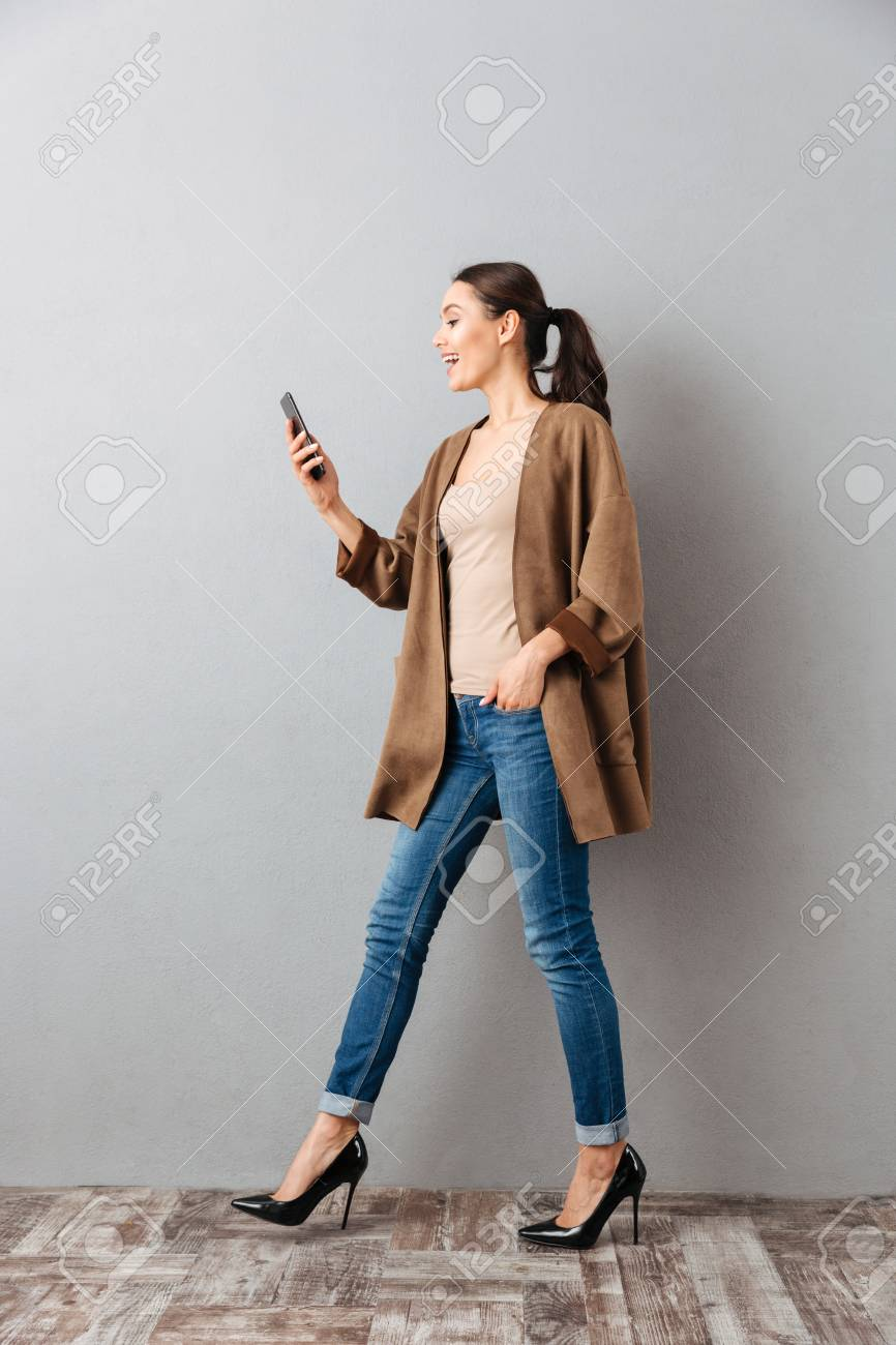 Full length of a happy young asian woman using mobile phone while walking over gray background - 95029487