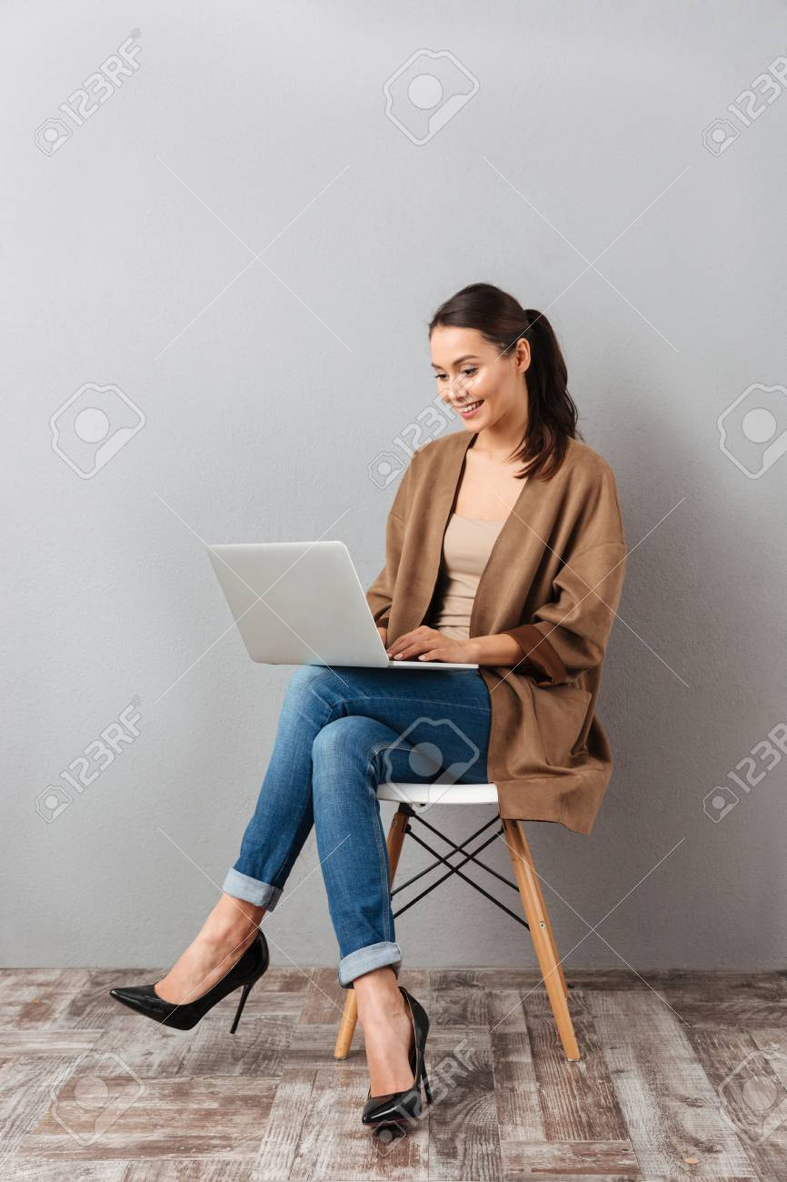 Full length portrait of a happy casual asian woman holding laptop computer while sitting on a chair over gray background - 95029628
