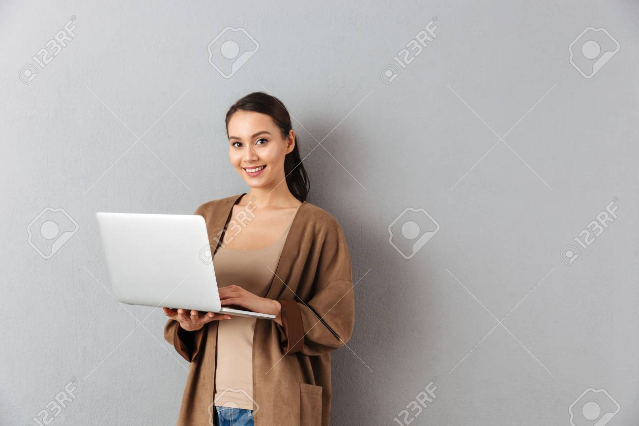 Portrait of a happy young asian woman holding laptop computer while standing and looking at camera over gray background - 95133518