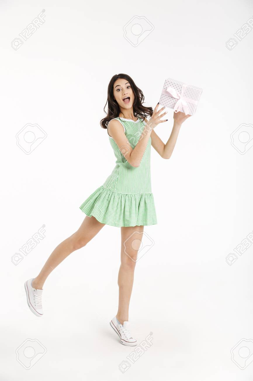 Full length portrait of a joyful girl dressed in dress standing and holding gift box isolated over white background - 95041456
