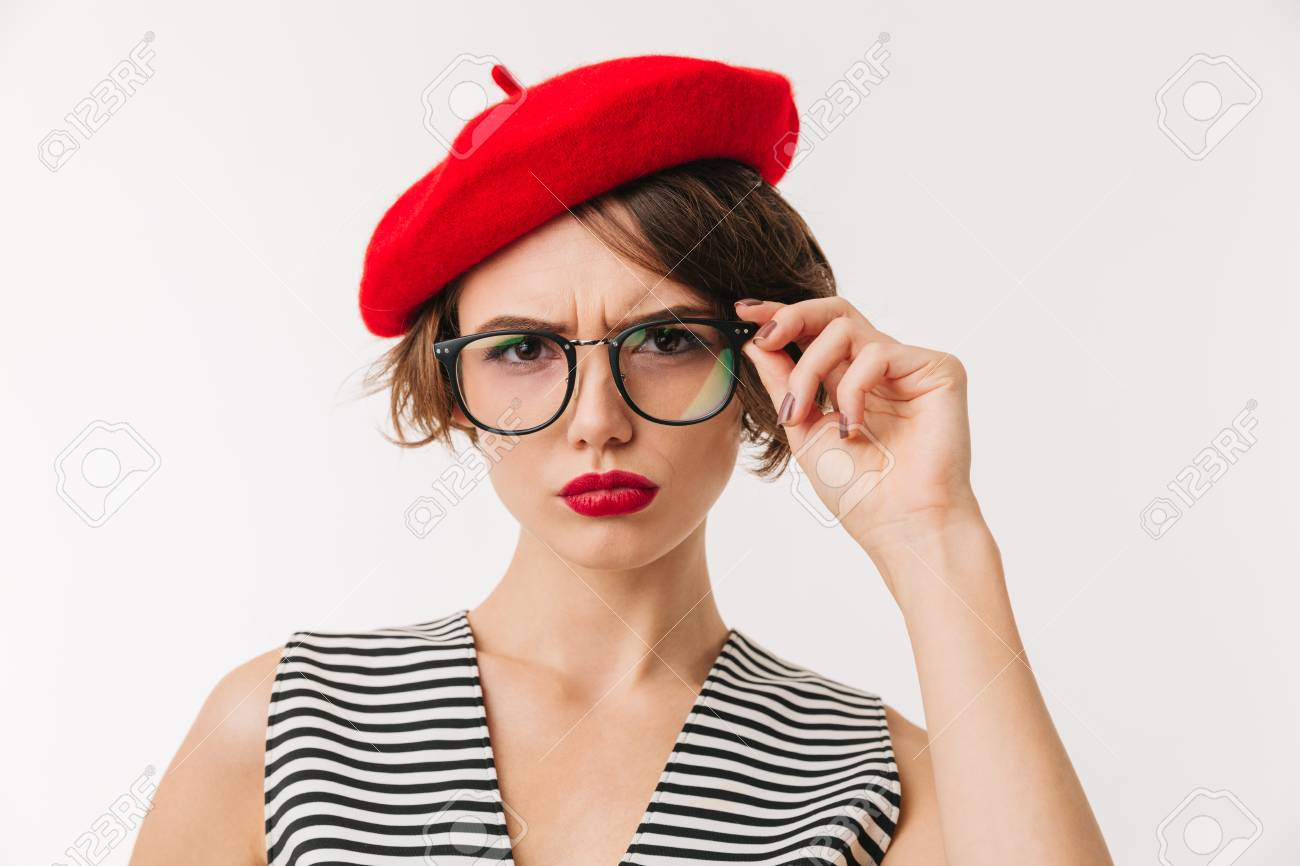 Portrait of an upset woman wearing red beret and eyeglasses looking at  camera isolated over white c193d5cce03