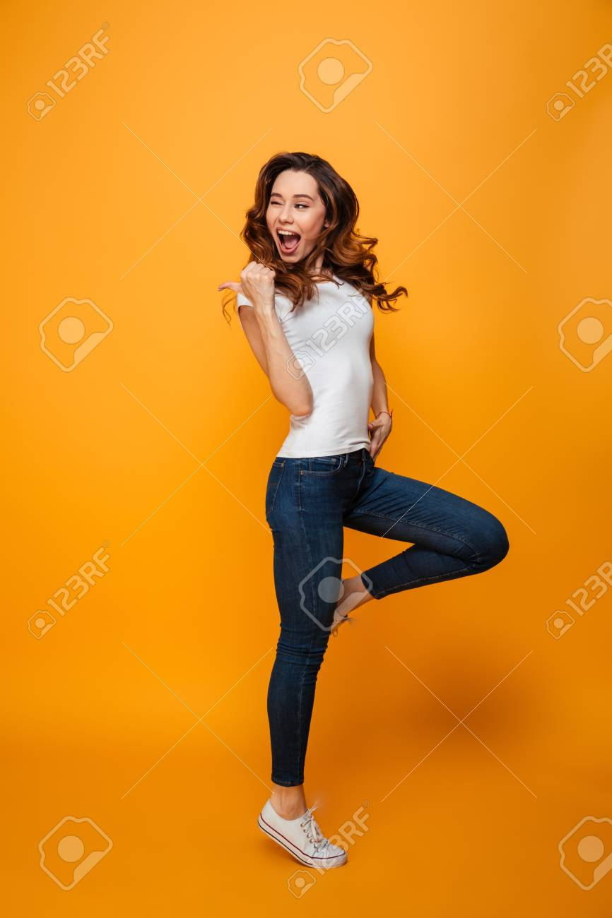Full length image of Joyful brunette woman in t-shirt jumping and winks while looking and pointing away with thumb over yellow background - 96270838