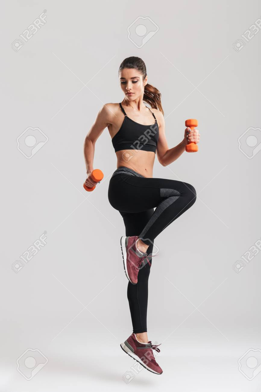 Full-length photo of sporty woman workout with small dumbbells isolated over gray background - 96272602
