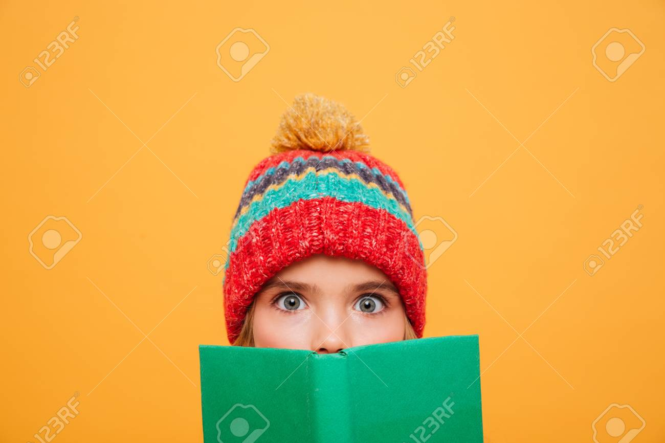 90c7886a247 Close up image of Surprised Young girl in sweater and hat hiding behind the  book and