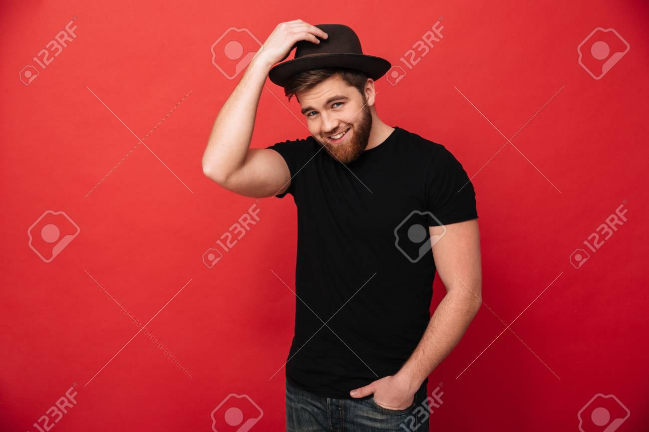 b0ea247a Portrait of handsome stylish man wearing black outfit touching his hat and  posing with hand in